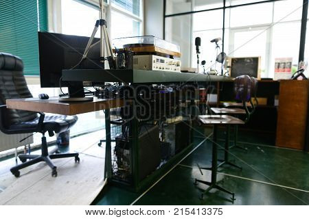 Taking Close-up on radio. In office, there are devices for recording of radio microphones and mixing consoles, broadcast processor and special device, computer on wooden table and chairs in radio studio with big panoramic windows. Concept of radio studio