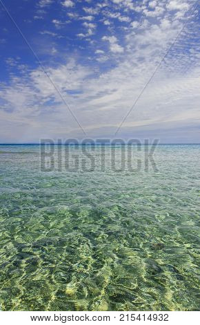 Apulia seascape: mediterranean sea. Salento: Alimini beach, Italy. Horizon dominated by clouds: in the distance  sailing boat and Albania mountains.