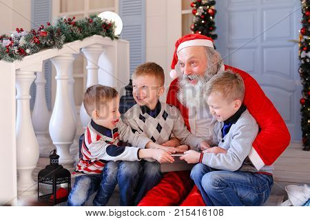 Santa Claus having fun with little mischievous boy and not presenting gift. Happy kids presented new tablet. Concept of joking Father Christmas with naughty child.