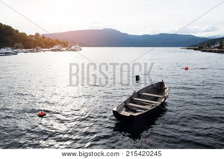 Wooden boat in the hardangerfjord fjord waters, Norway. Evening sunlight