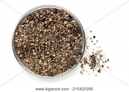Crushed black peppercorns, top view, isolated on white.