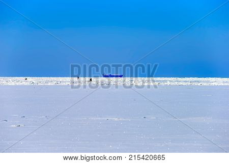 Fishermen on the ice of the Gulf of Finland not far from the ship going along the winter fairway