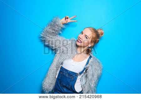 Attractive hipster girl in fluffy coat on color background