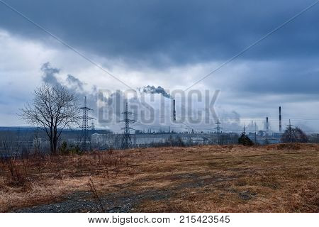 a dramatic landscape view of the factory which produces toxic fumes of smoke