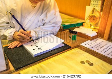 Nara, Japan - April 26, 2017: detail of Shinto Miko, maiden or priestess, while writing Japanese script with a brush for a faithful. Kasuga Taisha Sanctuary is Nara's most celebrated shrine