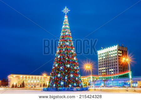 Gomel, Belarus. Xmas Christmas Tree In Lenin Square At Evening Or Night Illuminations Lights. Famous Place At Winter New Year Holiday Season.