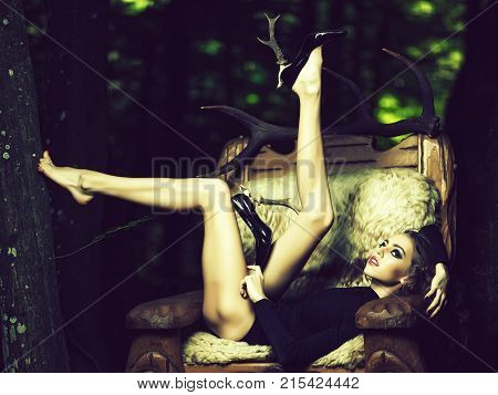 One beautiful young flexible sensual girl with long curly hair bright makeup and straing slim body in black underwear and shoes with heel of antlers sitting in big wooden arm chir with fur in forest