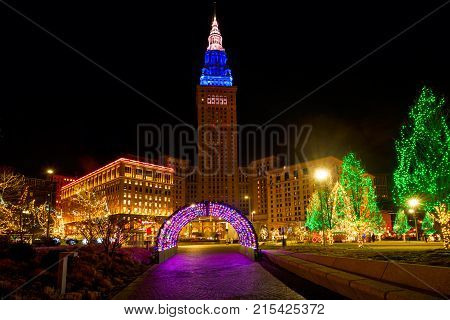 CLEVELAND OH - DECEMBER 30 2016: Cleveland's Terminal Tower lit up for Christmas stands over brightly lit holiday displays on Public Square.