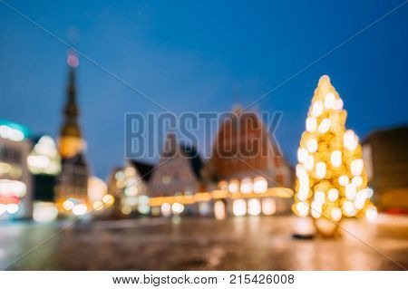 Riga, Latvia. New Year Boke Lights Xmas Christmas Tree Decoration And Festive Illumination Of Town Hall Square. Defocused Blue Bokeh Background Effect. Design Backdrop.