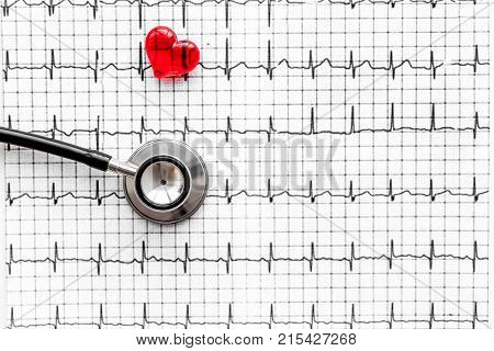 Examine the heart to prevent heart disease. Heart sign and stethoscope on cardiogram background top view.