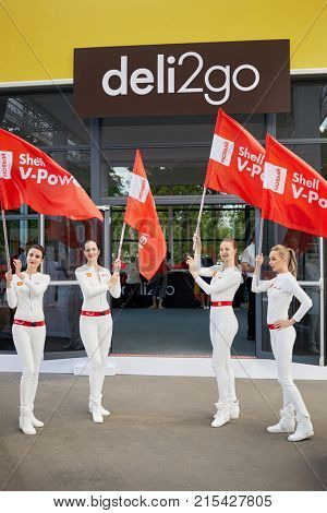 MOSCOW, RUSSIA - JUN 18, 2017: Four girls with Shell V-Power flags against entry to deli2go cafe at VDNKH during summer festival dedicated to 125th anniversary of Shell in Russia.