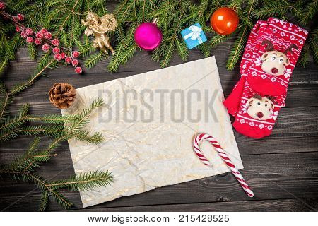 Christmas fir tree branches Christmas balls decorations angel candy cane cone and christmas socks frame an old paper copy space for text. Can be used for Christmas or new year project.