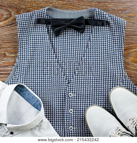 Man's classic clothes outfit flat lay with formal shirt, vest, bowtie, shoes. Top view