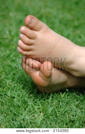 Two little white healthy feet of a caucasian child resting barefeet in the grass of a tidy lawn in the sunshine outdoors during summertime poster