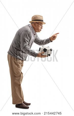 Full length profile shot of an angry mature man holding a deflated football and scolding someone isolated on white background