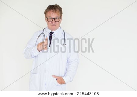 Closeup portrait of content middle-aged male doctor looking at camera, pointing at viewer and standing with one hand in pocket. Isolated front view on white background.