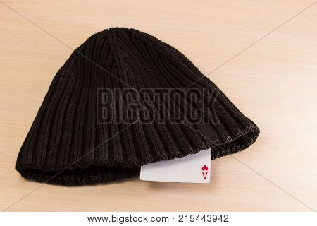 card ace sticking out of a sports winter cap on a wooden background is a symbol of success and significance