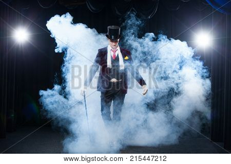 Magician, Juggler man, Funny person, Black magic, Illusion standing on the stage with a cane of beautiful light. shrouded in a beautiful mysterious smoke.