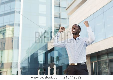 Happy excited black businessman celebrate victory with fists raised in the air. Winner, successful african-american man outdoors against modern glass office center background, lifestyle portrait