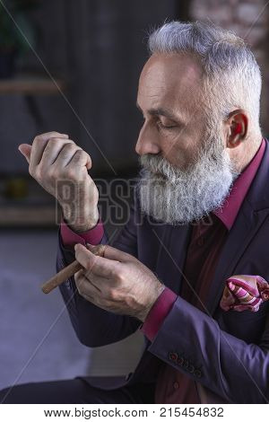 Side view serene bearded retire buttoning cuff link on sleeve of elegant shirt while keeping tobacco in arm. Appearance concept