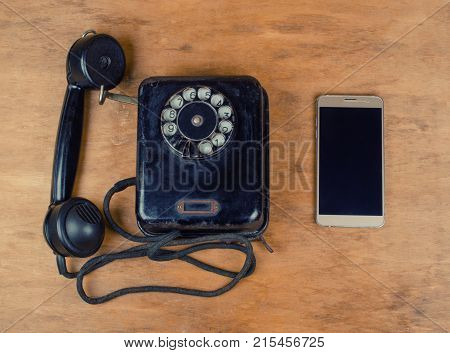 Black vintage phone and a new modern mobile phone on an old wooden background top view retro style (old and new concept)