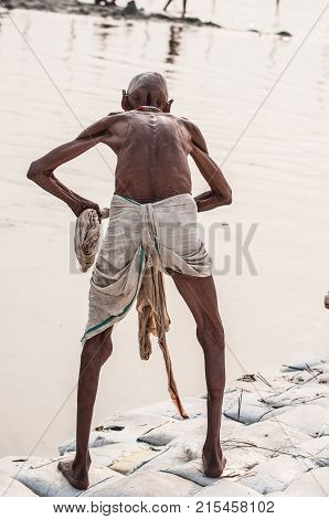 hindu pilgrim washes himself in the holy water of the ganges river in india poster