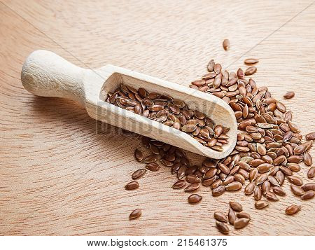 Flax seeds in a wood spoon on a wooden background. Flaxseed is scattered from a scoop.
