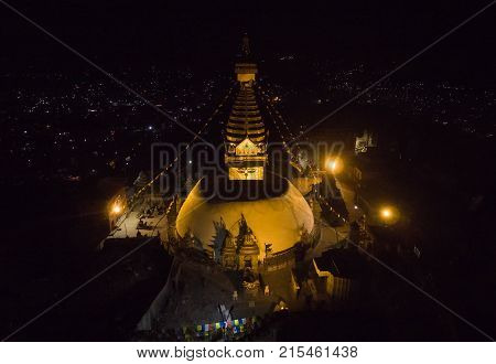 The top view of the sacred ancient stupa of Svayambhu shining gold in night-time lighting of searchlights over Kathmandu Valley.