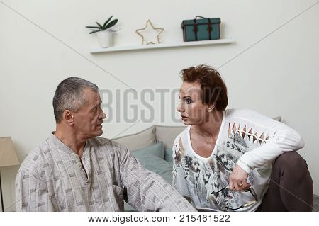 Picture Of Mature Caucasian Couple Wearing Casual Clothes Having Fight In Bedroom: Suspicious Female