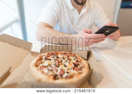 A box of appetizing pizza is on the table. A man uses a phone on the background of an open box of tasty pizza. Focus on pizza