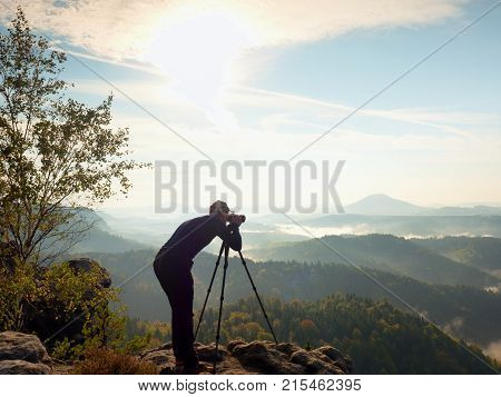 Photographer  On Cliff. Nature Photographer Takes Photos With Mirror Camera On Peak Of Rock.