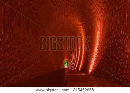 Empty long arched brick pedestrian tunnel Prague. Orange brick walls strip of lighting lamp. Bright arch. Underground mysterious footpath for walkers. Underpass and nature at end of tunnel concept
