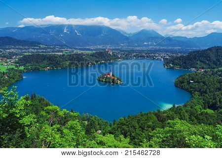 Aerial view of Lake Bled Alps Slovenia Europe. Mountain alpine lake. Island with church in Lake Bled. Summer landscape. Castle and mountains in background. Famous travel destination of Slovenia