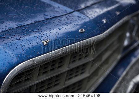 MOSCOW, RUSSIA - AUGUST 26, 2017: Ford car logo on a vintage car close-up, selectiv focus. Retro cars festival. Rainy evening, real dark background