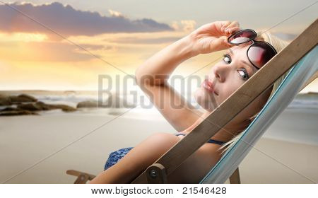 Beautiful woman in swimsuit lying on a deckchair at the seaside