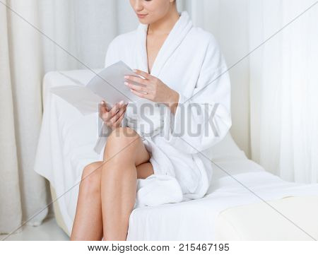 Calm young woman is reading beauty journal while relaxing after spa procedure. She is sitting on comfortable daybed in lounge