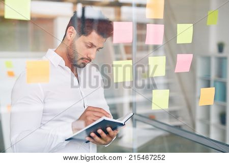 Serious employee standing by note board and rewriting organization moments into his notebook
