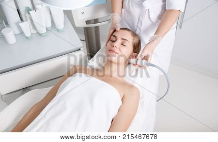 Top view of serene young woman getting skin rejuvenation treatment. She is lying on massage table at spa and smiling. Cosmetologist is lifting laser on her face