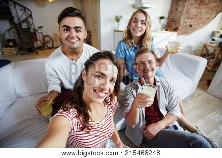 Happy girl making selfie with friends during home party