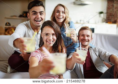 Smiling friends with drinks cheering at camera while relaxing at home during get-together
