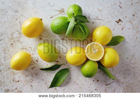 Fresh green lemons with leaves on table. Lemons on twig with leaves. Ripe and unripe lemon with leaves.