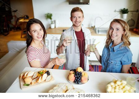 Two girls and guy with glasses of drink looking at camera at home party