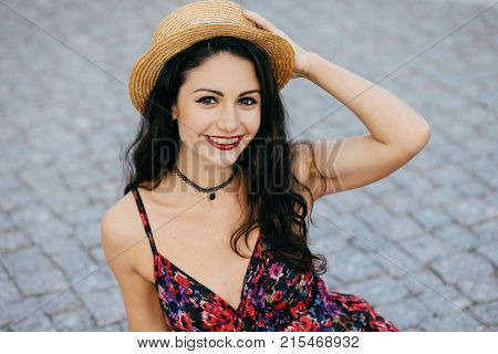 Fashionable Pretty Brunette Female With Make-up Wearing Straw Hat On Head And Summer Dress Smiling P