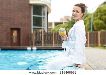 Attractive young woman with glass of juice enjoying her vacation at spa resort