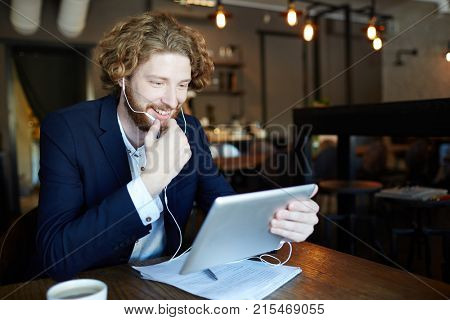 Happy businessman with tablet and earphones talking through video-chat in cafe