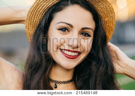 Close Up Portrait Of Cute Female With Dark Hair, Charming Eyes And Pleasant Smile Wearing Straw Summ