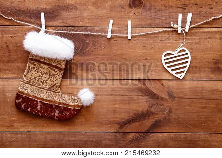 Christmas Stocking And White Heart Hanging On Brown Wooden Background, Top View