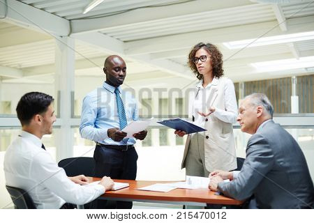 Mature and young businessmen discussing reports of their intercultural colleagues at briefing