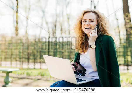 Attractive Woman With Trendy Hairdo Sitting In Park Communicating Over Her Cell Phone Using Modern L