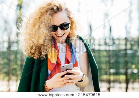 Beautiful Young Female In Fashionable Round Shades Texting Messages To Her Friends Via Social Networ